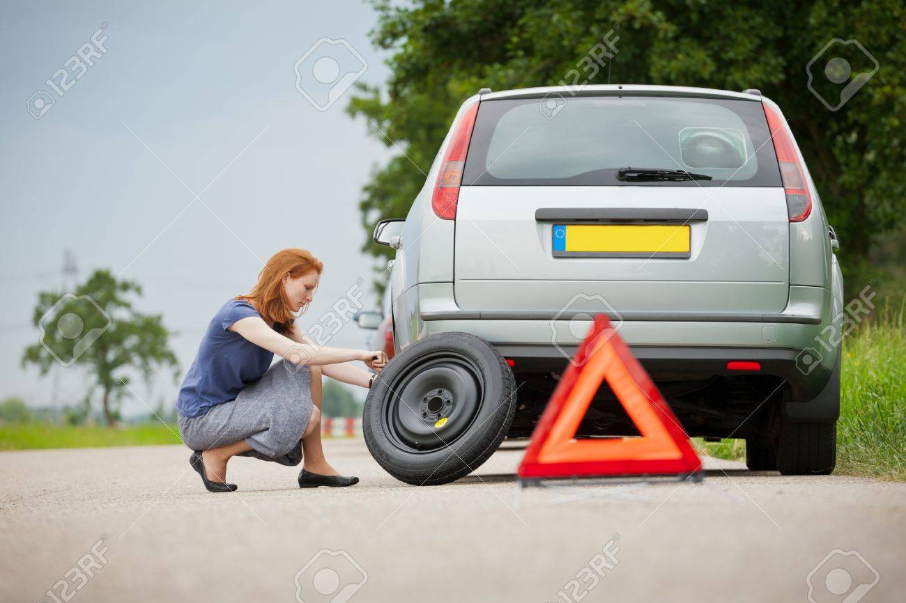Young female driver changing a flat tire on her car. Standard-Bild - 20467536