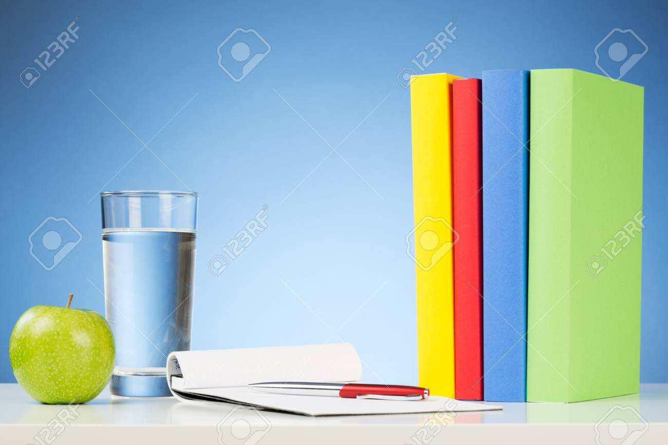 Un Escritorio Con Libros De Colores, Un Vaso De Agua, Una Manzana ...