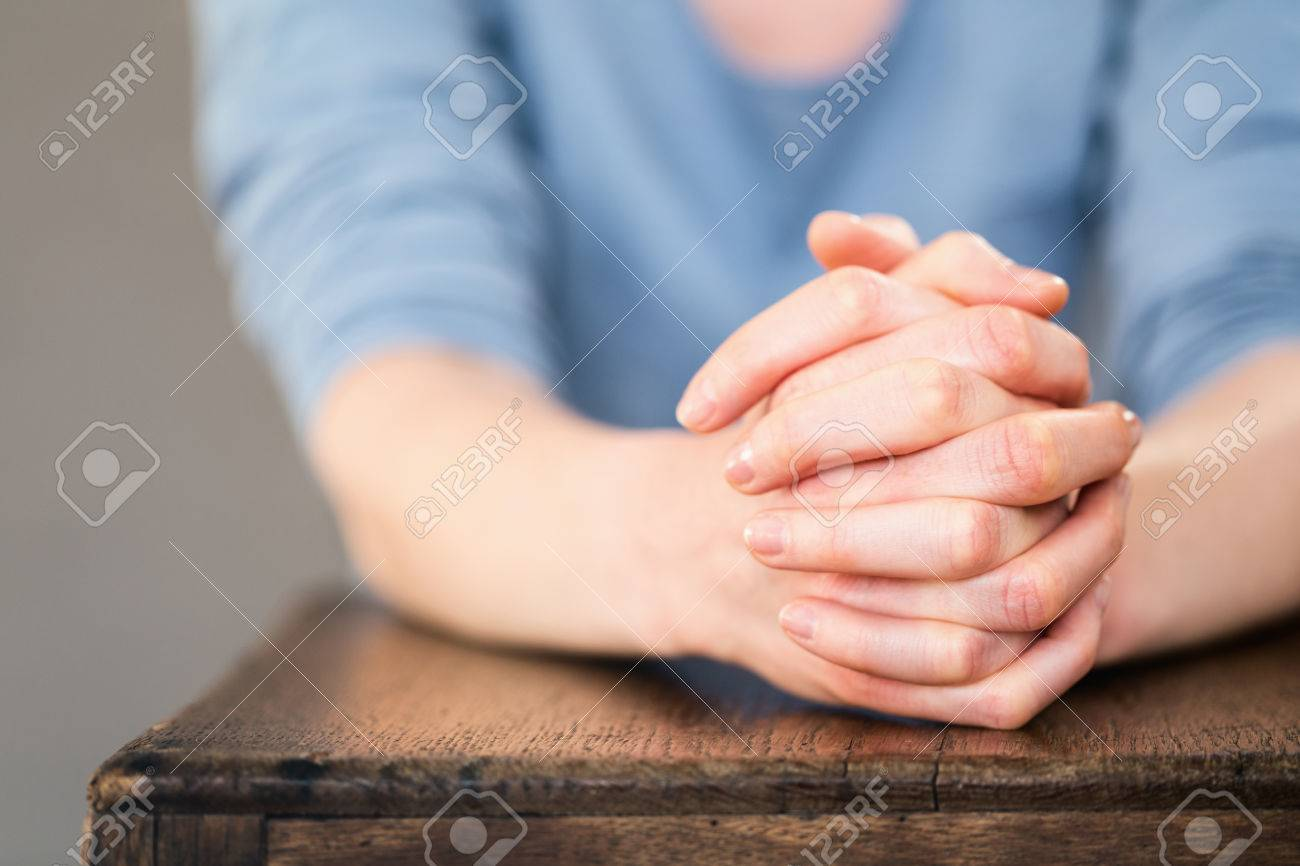Praying Hands Of A Young Woman Over An Old Wooden Table Or Chair