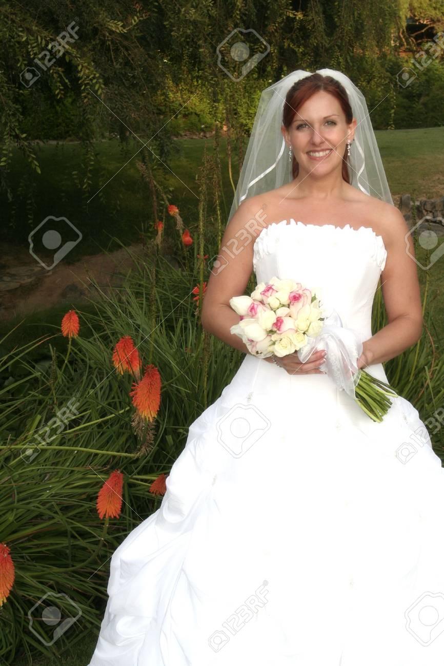 bride poses by orange flowers - 1686747