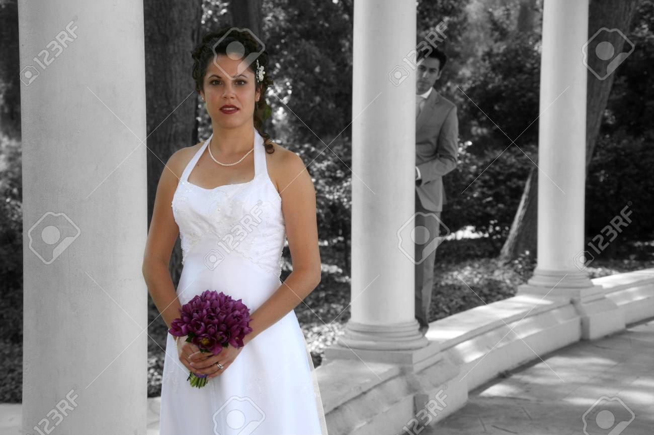 bride poses while groom is in the background - 1686790