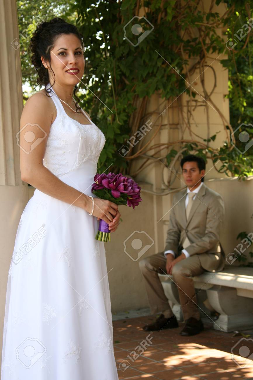 bride poses for a photo while groom sits in the background - 1686783