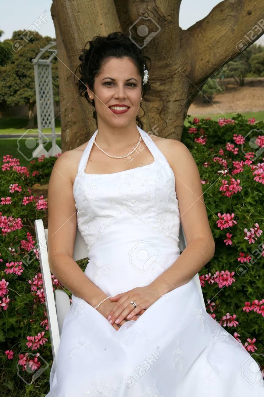 bride sits in a flower garden - 1686816