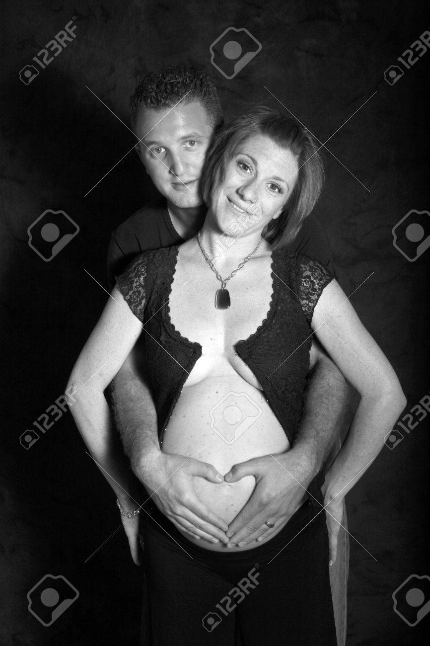 dad places a heart over moms pregnant belly - 1686802