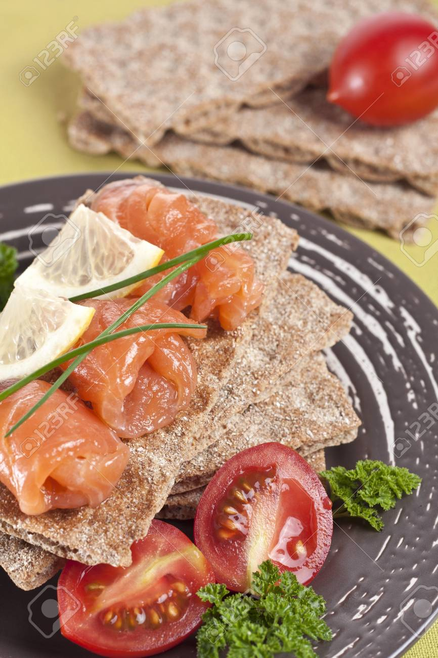 snack from a salmon with crispbread, vegetables and a lemon Stock Photo - 19568756
