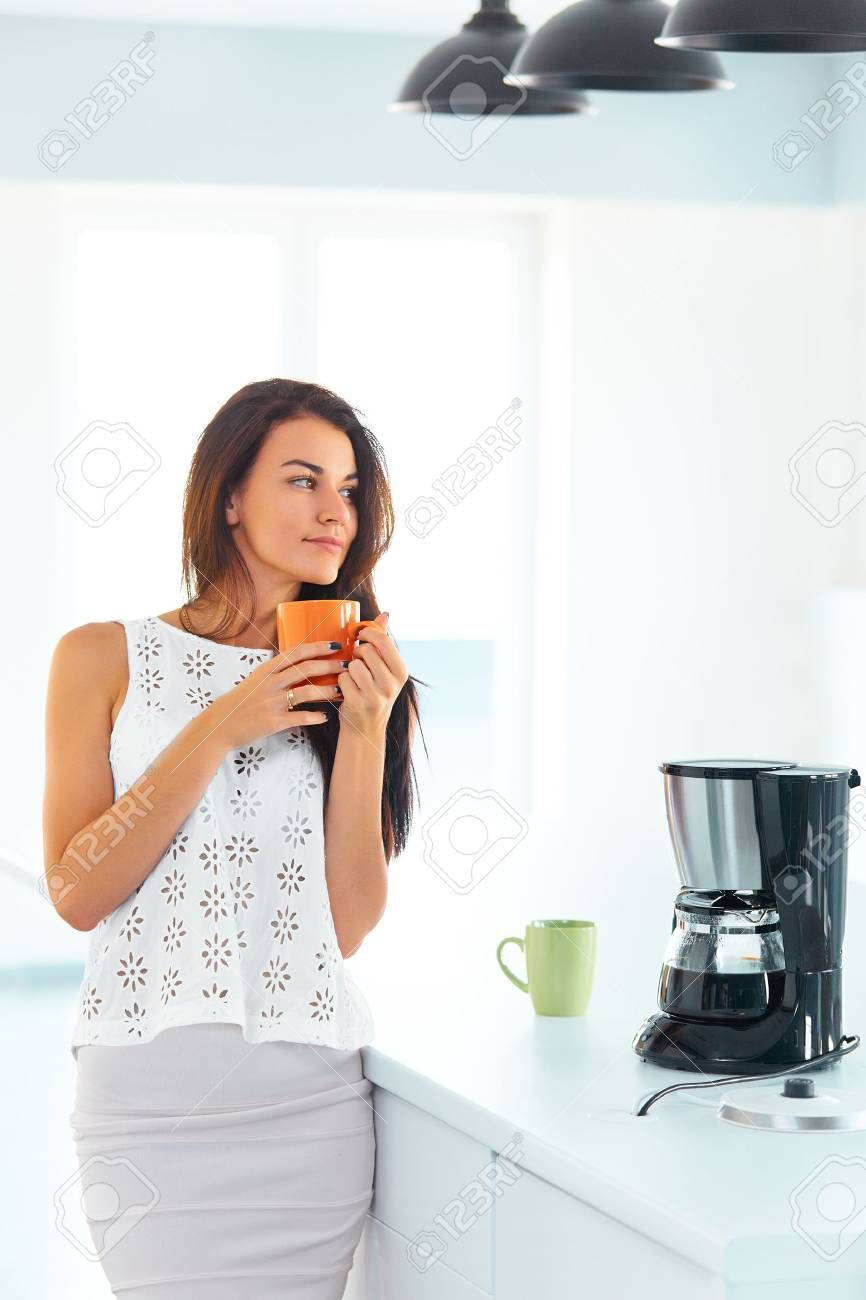Happy Attractive Woman Holding A Cup Of Hot Coffee In Her Hands ...