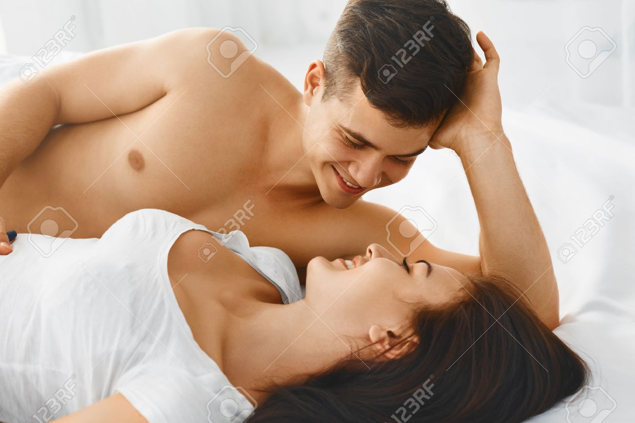 Close up portrait of a young romantic couple hugging and kissing  laying  down on a. Close Up Portrait Of A Young Romantic Couple Hugging And Kissing