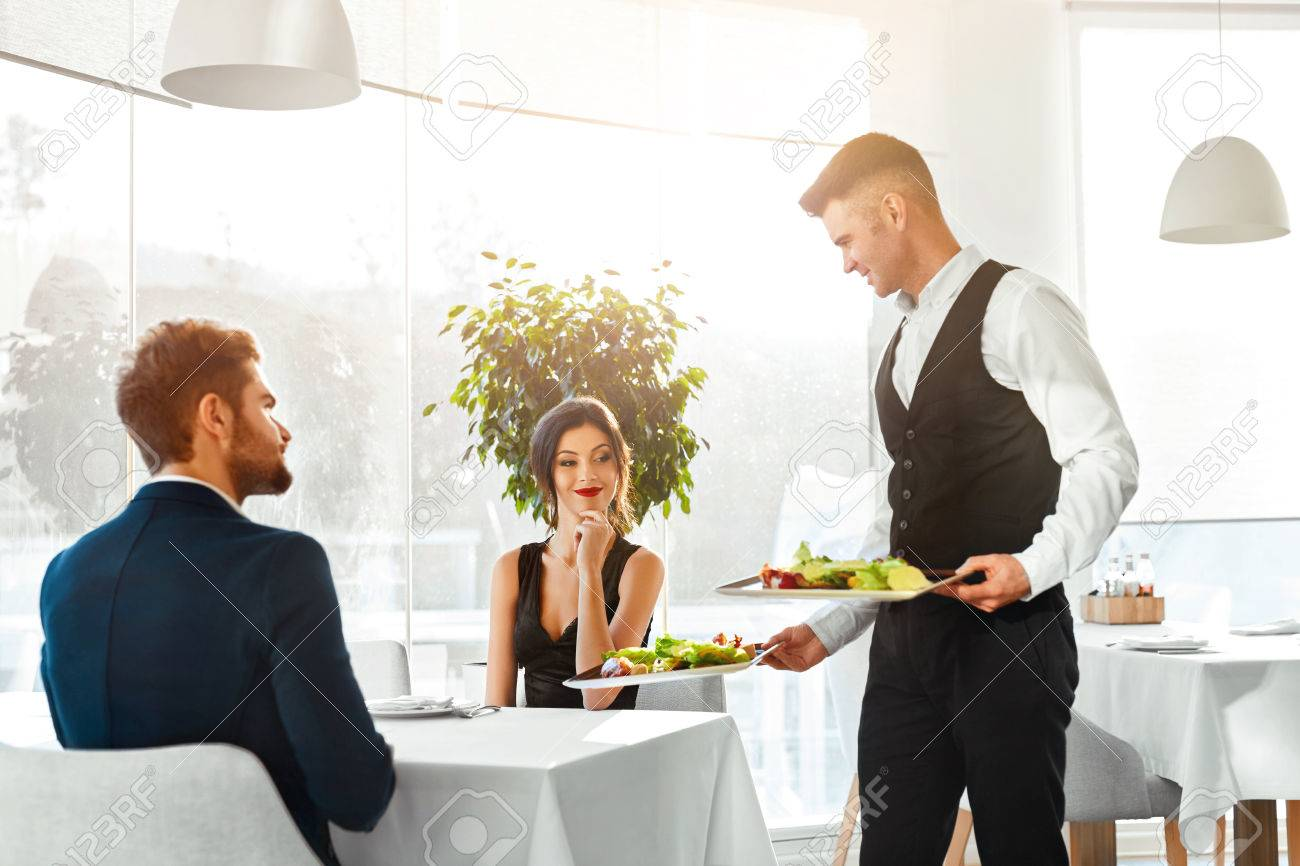Happy Couple In Love Having Romantic Dinner In Luxury Gourmet Restaurant. Waiter Serving Meal. People Celebrating Anniversary Or Valentine's Day. Romance, Relationship Concept. Healthy Food Eating. Stock Photo - 49920877