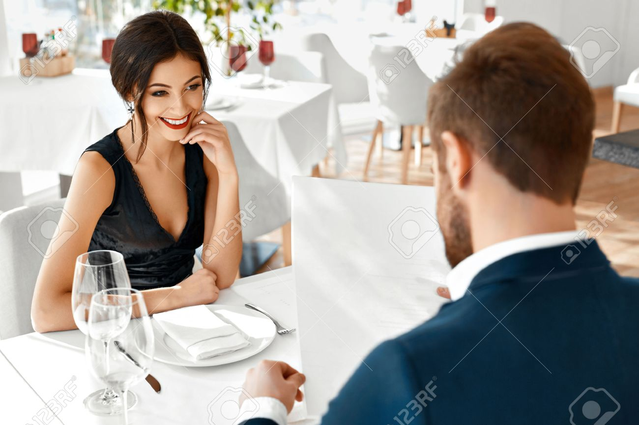 Romantic Couple In Love Having Dinner In Luxury Gourmet Restaurant. Happy Beautiful Lovely People Reading Menu, Choosing Food, Celebrating Anniversary Or Valentine's Day. Romance And Relationships. Stock Photo - 49920931