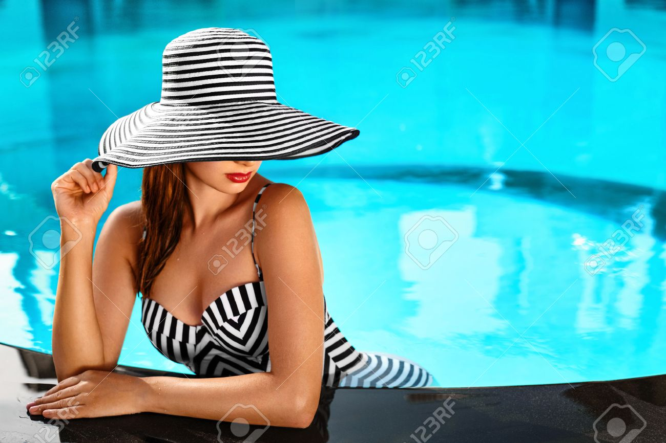 Summer Woman Body Care. Beautiful Sexy Girl With Healthy Skin In Elegant Striped Bikini, Sun Hat Relaxing In Swimming Pool Water In Resort Spa Hotel On Travel Holidays Vacation. Enjoyment. Lifestyle - 52696575