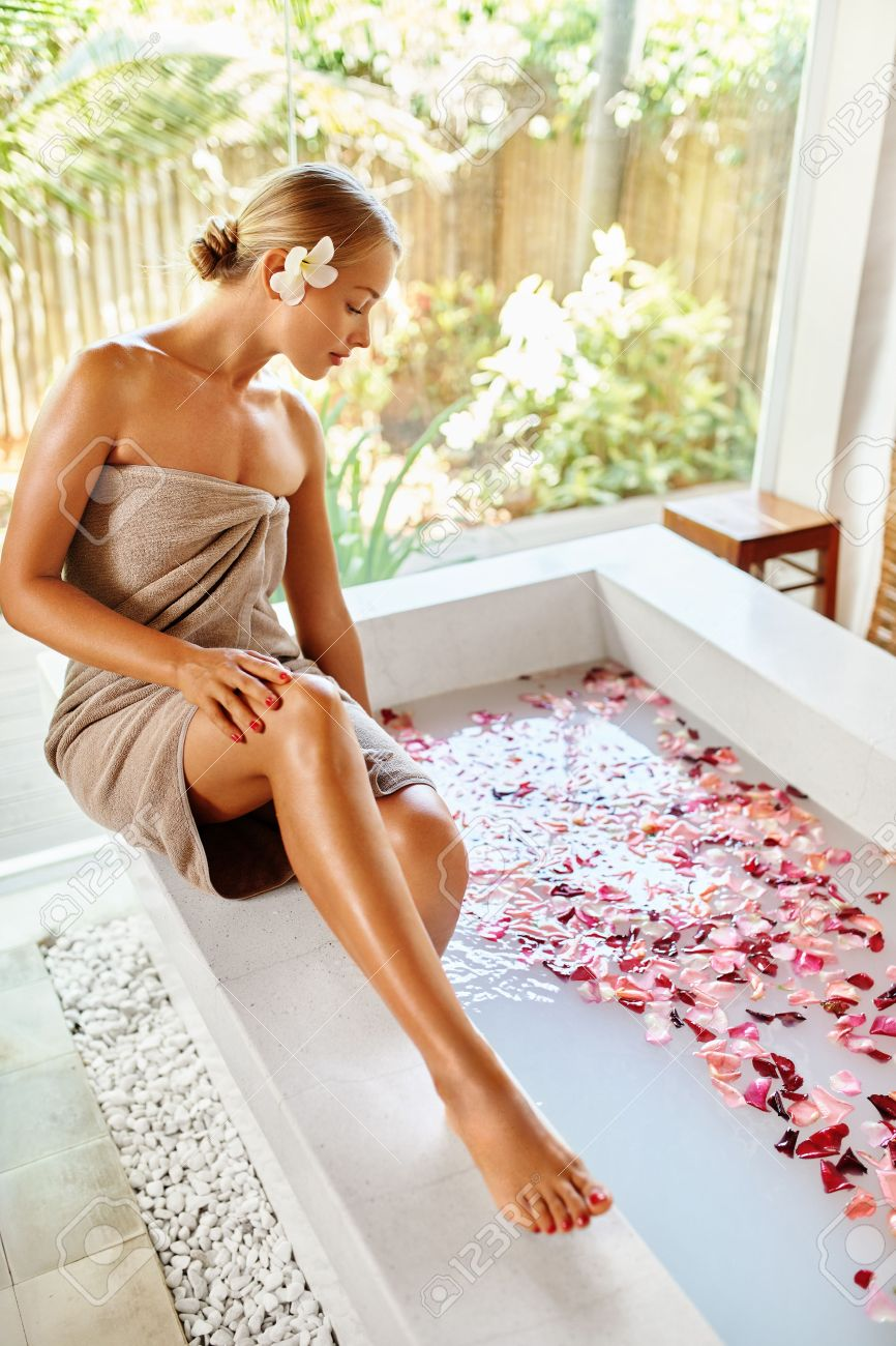 Stock Photo - Woman Spa Body Care Treatment. Beautiful Sexy Blonde Girl In  Towel Sitting Near Flower Rose Bath In Day Spa Salon.