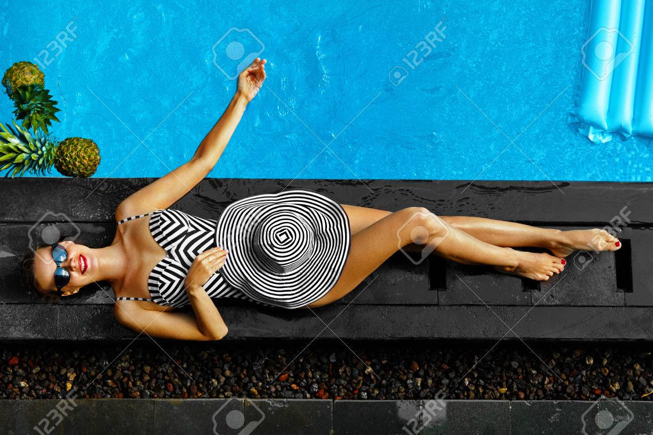 Woman Summer Fashion. Happy Sexy Smiling Girl With Fit Body, Long Legs, Healthy Skin In Bikini, Sun Hat, Sunglasses Sunbathing By Swimming Pool On Travel Holidays Vacation. Beauty, Wellness, Lifestyle - 55831729