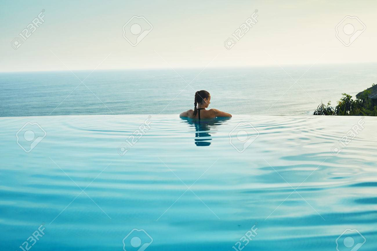 Luxury Resort. Woman Relaxing In Infinity Swimming Pool Water...