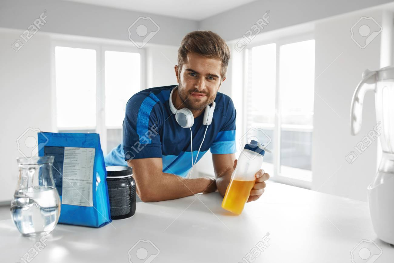 Sports Energy Drink. Handsome Healthy Happy Man With Fit Muscular Body In Sportswear, Headphones With ????, Amino Acid Beverage And Bodybuilding Nutrition Supplements In Kitchen Before Fitness Workout Stock Photo - 58911391
