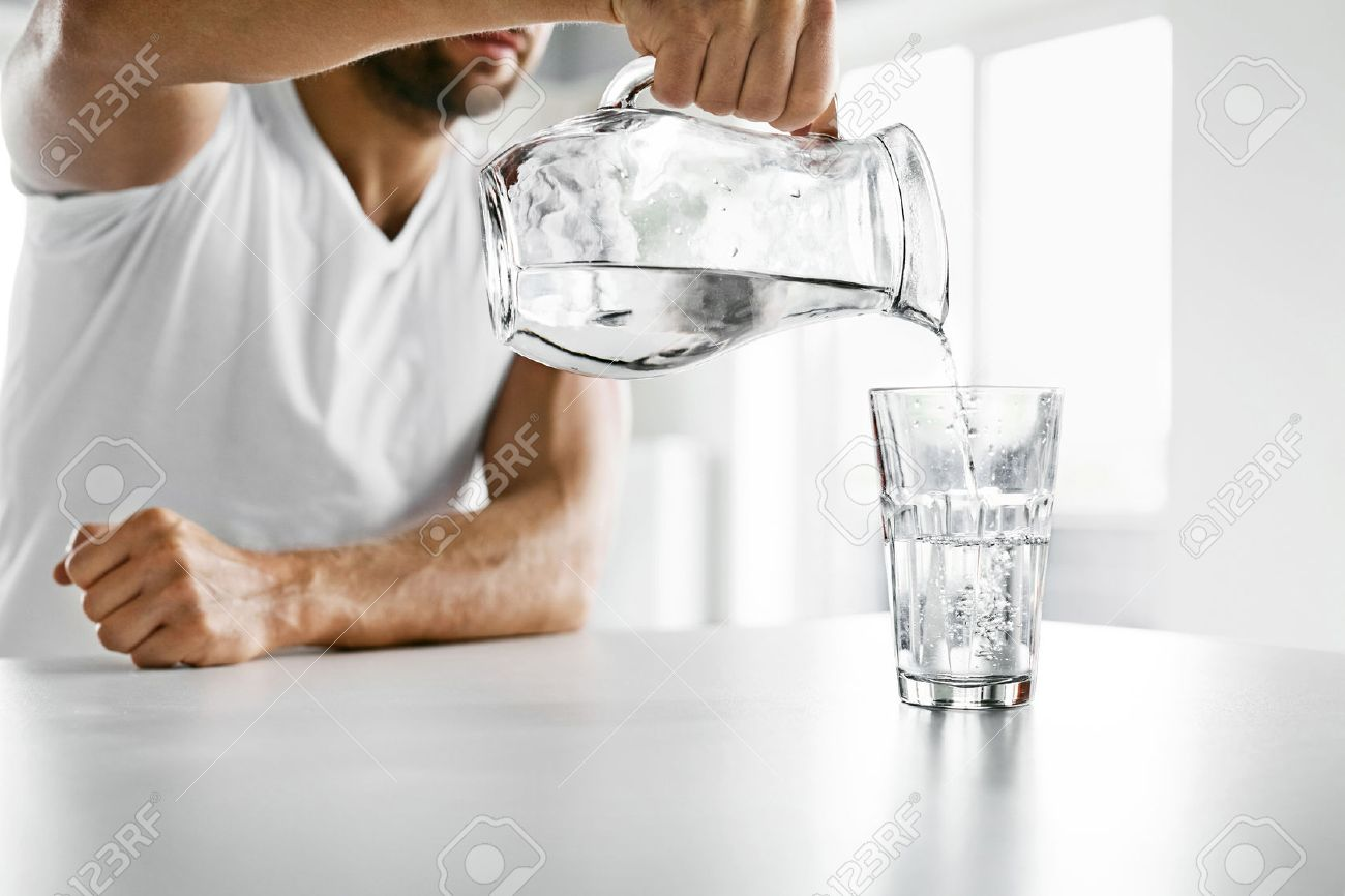 b8cbd487da9c Drink Water. Close Up Of Handsome Young Man Pouring Fresh Pure Water From  Pitcher Into