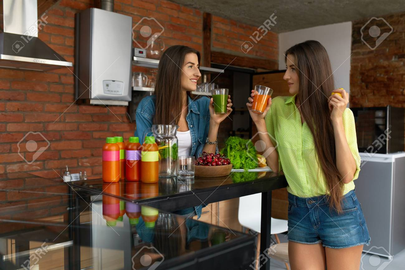 Healthy eating women drinking fresh detox juice green smoothie in kitchen beautiful happy fit girls enjoying vegetable drinks bottles standing on table