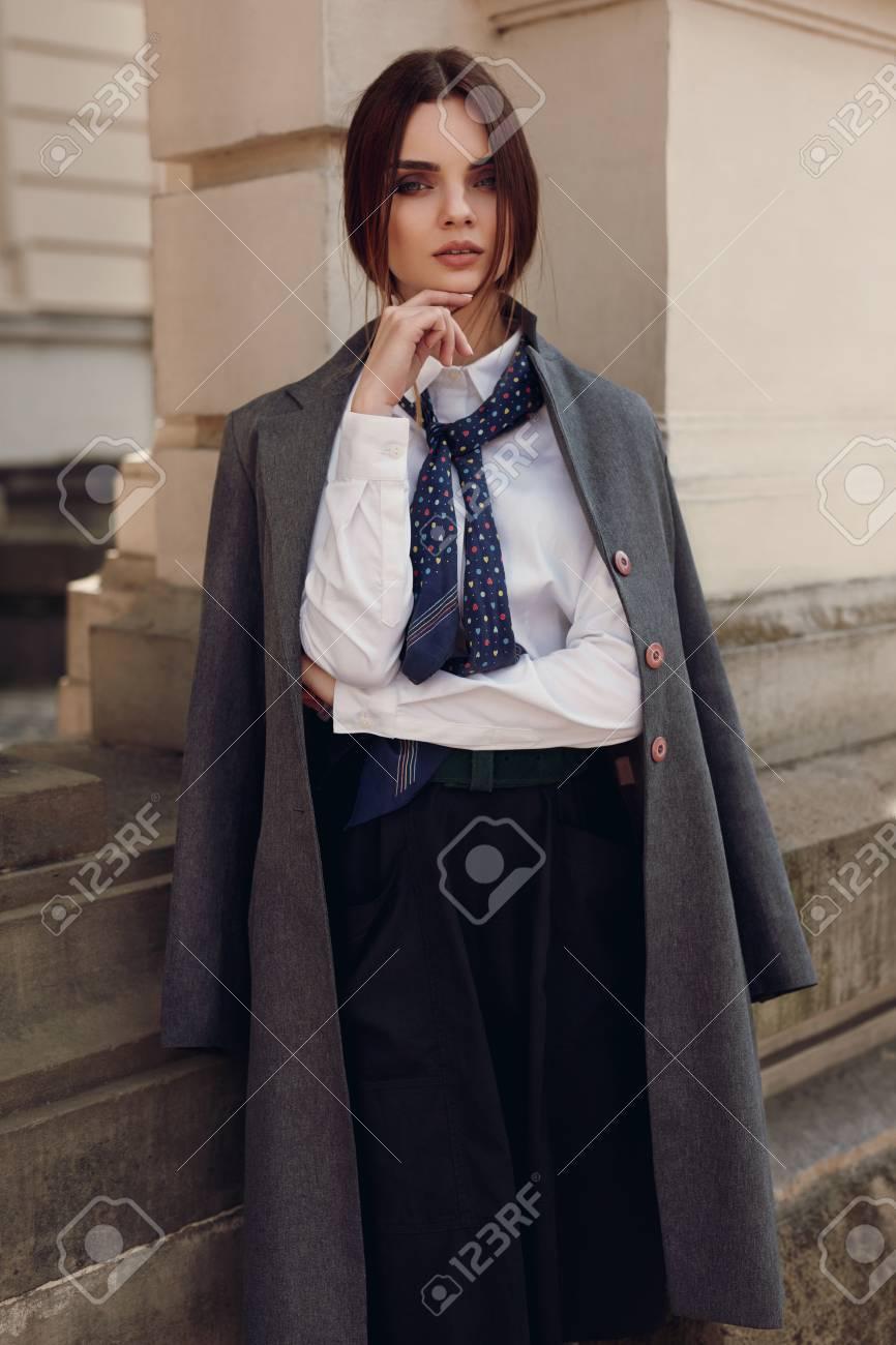 628d95911 Caída de la mujer. Modelo femenino en la ropa de moda: En elegante  chaqueta, camisa, falda, corbata posando en la calle en otoño. Hermoso  atractivo ...