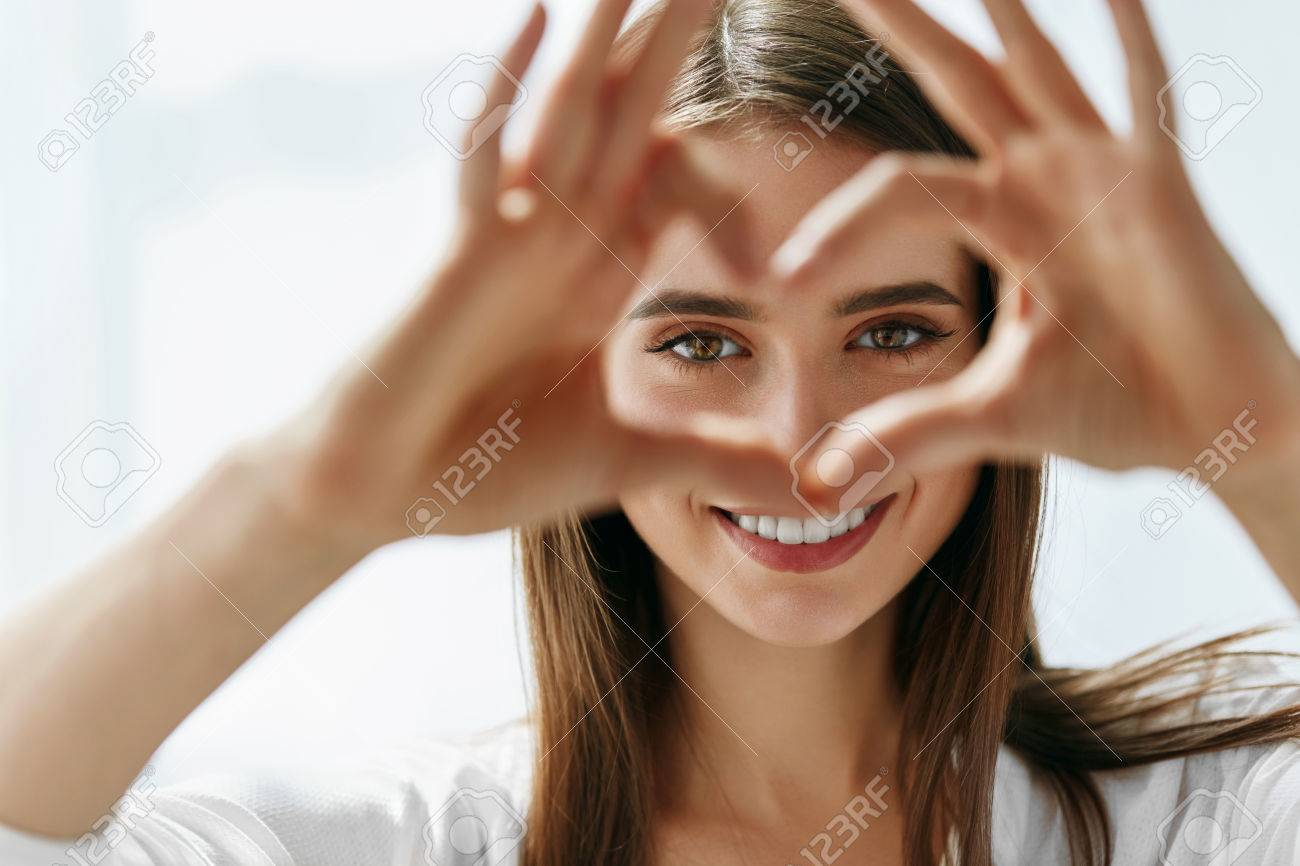 Healthy Eyes And Vision. Portrait Of Beautiful Happy Woman Holding Heart Shaped Hands Near Eyes. Closeup Of Smiling Girl With Healthy Skin Showing Love Sign. Eyecare. High Resolution Image Stock Photo - 68983638