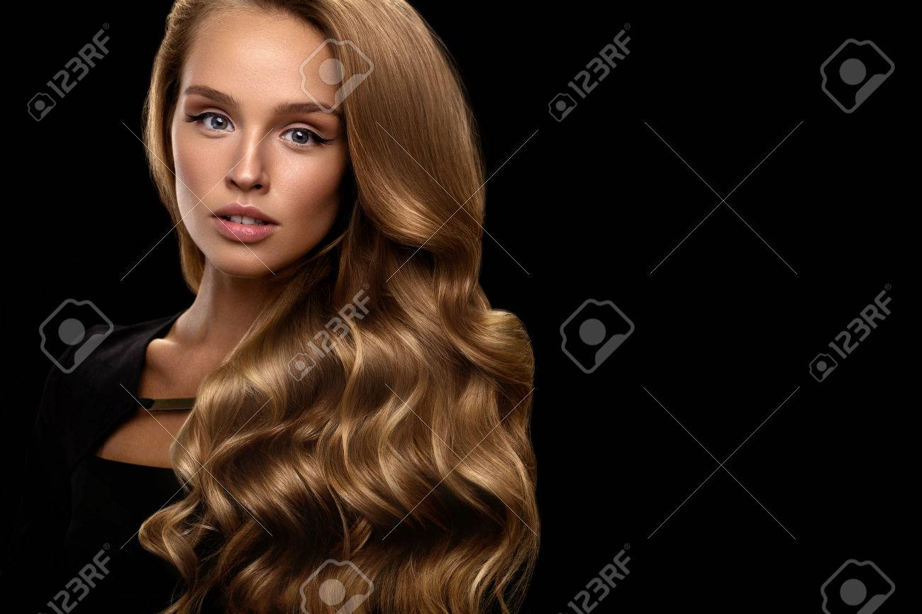 Hair Beauty And Makeup. Beautiful Fashion Girl Model With Perfect Blonde Hair Color And Gorgeous Face. Attractive Sexy Woman With Healthy Long Shiny Wavy Curly Hair Posing In Studio. High Resolution - 70474546