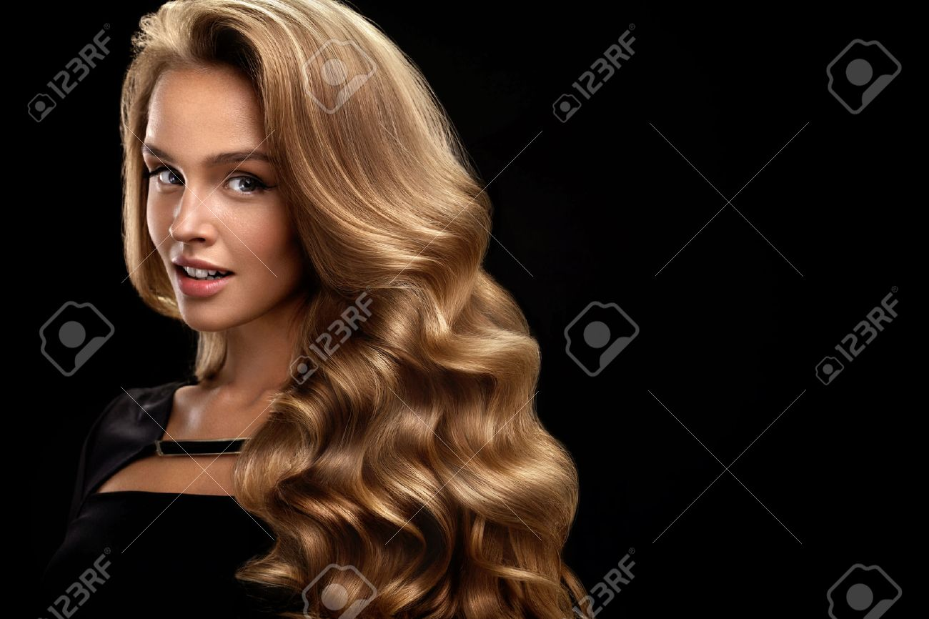 Beautiful Curly Hair. Female Beauty Model With Perfect Makeup, Gorgeous Volume And Blonde Hair Color. Attractive Smiling Woman With Healthy Long Shiny Wavy Hair On Black Background. High Resolution - 70993148