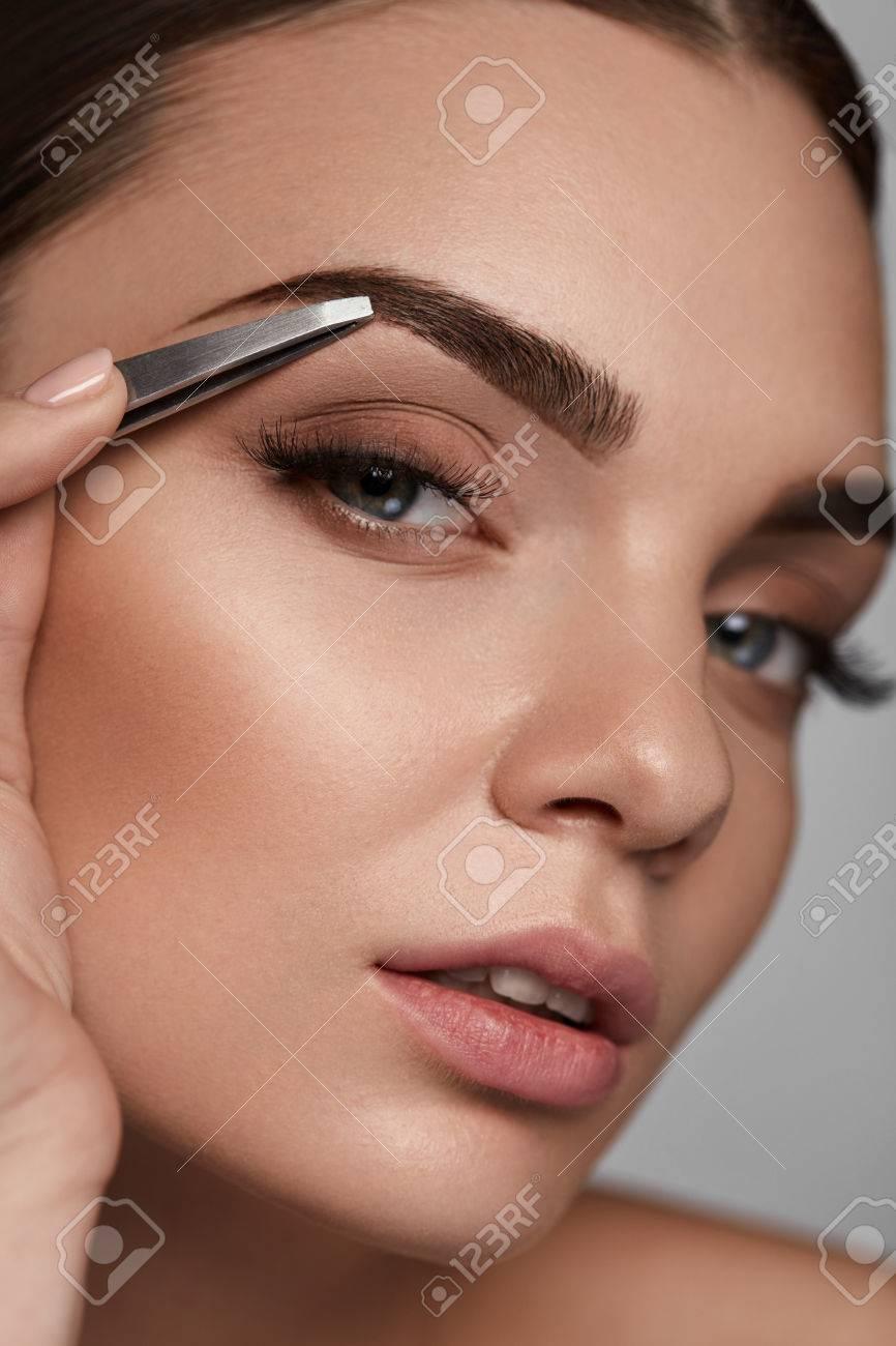 Corrección De Cejas Detalle De La Hermosa Mujer Joven Con Maquillaje Perfecto Y Largas Pestañas Depilarse Las Cejas Retrato De La Hembra Atractiva De La Cara Del Modelo Y Pinzas Cerca De