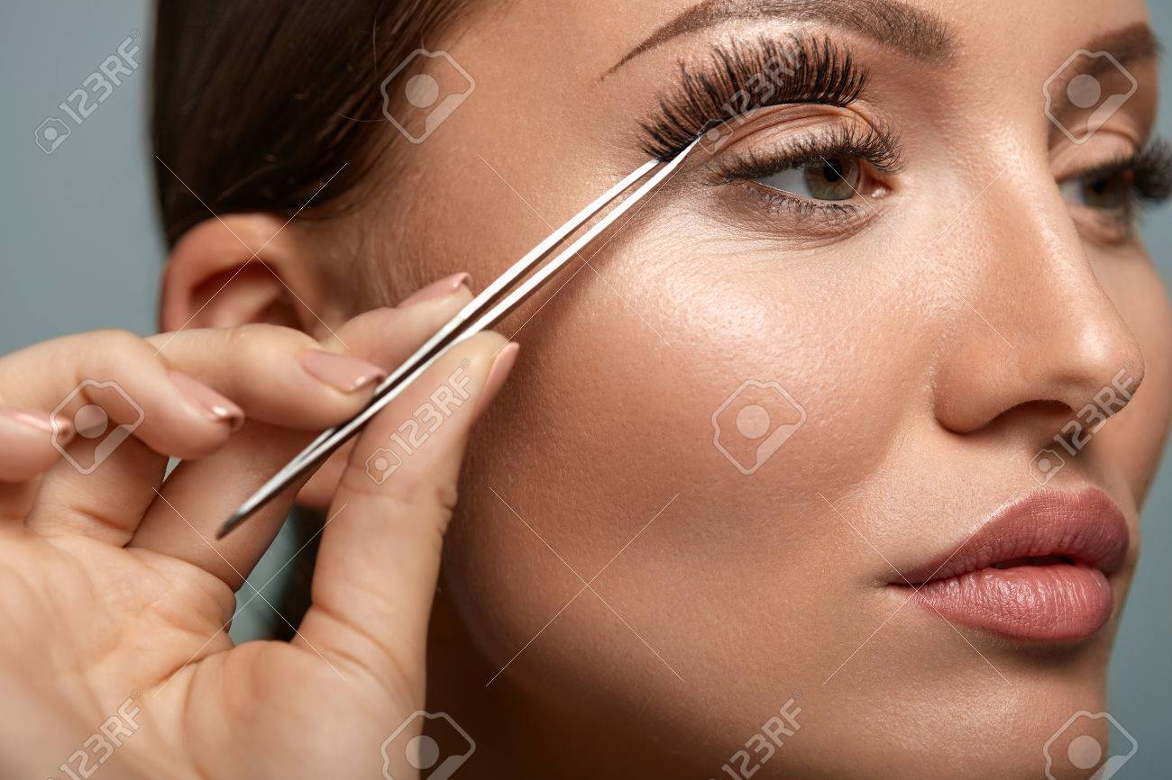 3bc97d81eea Eyelashes. Beautiful Woman Applying False Eyelashes With Tweezers. Closeup  Of Young Female Model Face