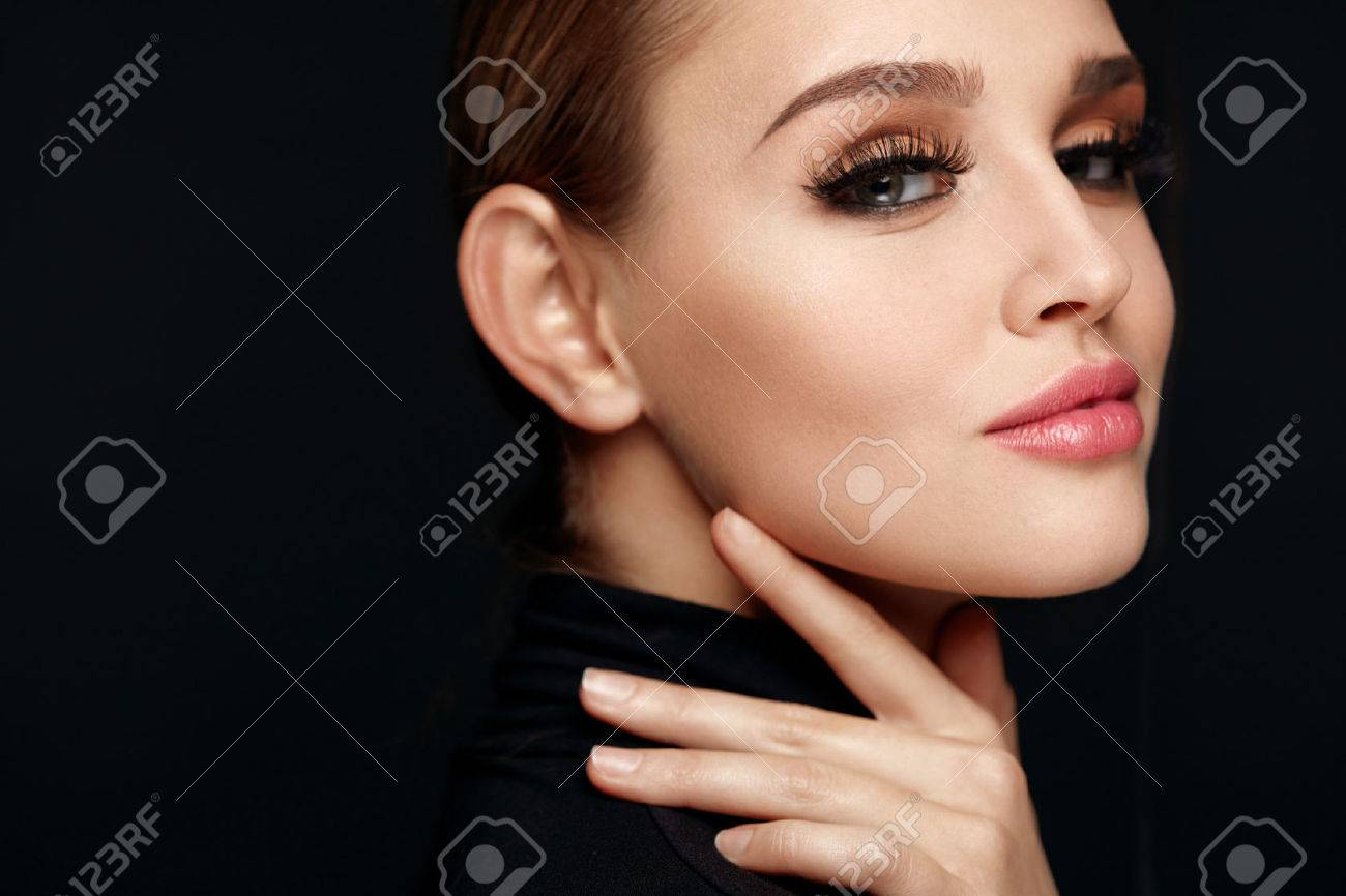 Beauty Makeup. Closeup Of Beautiful Smiling Woman Touching Soft Smooth Facial Skin. Portrait Of Sexy Young Female Model With Professional Make-up And Long Black Eyelashes. Cosmetics. High Resolution - 71353306