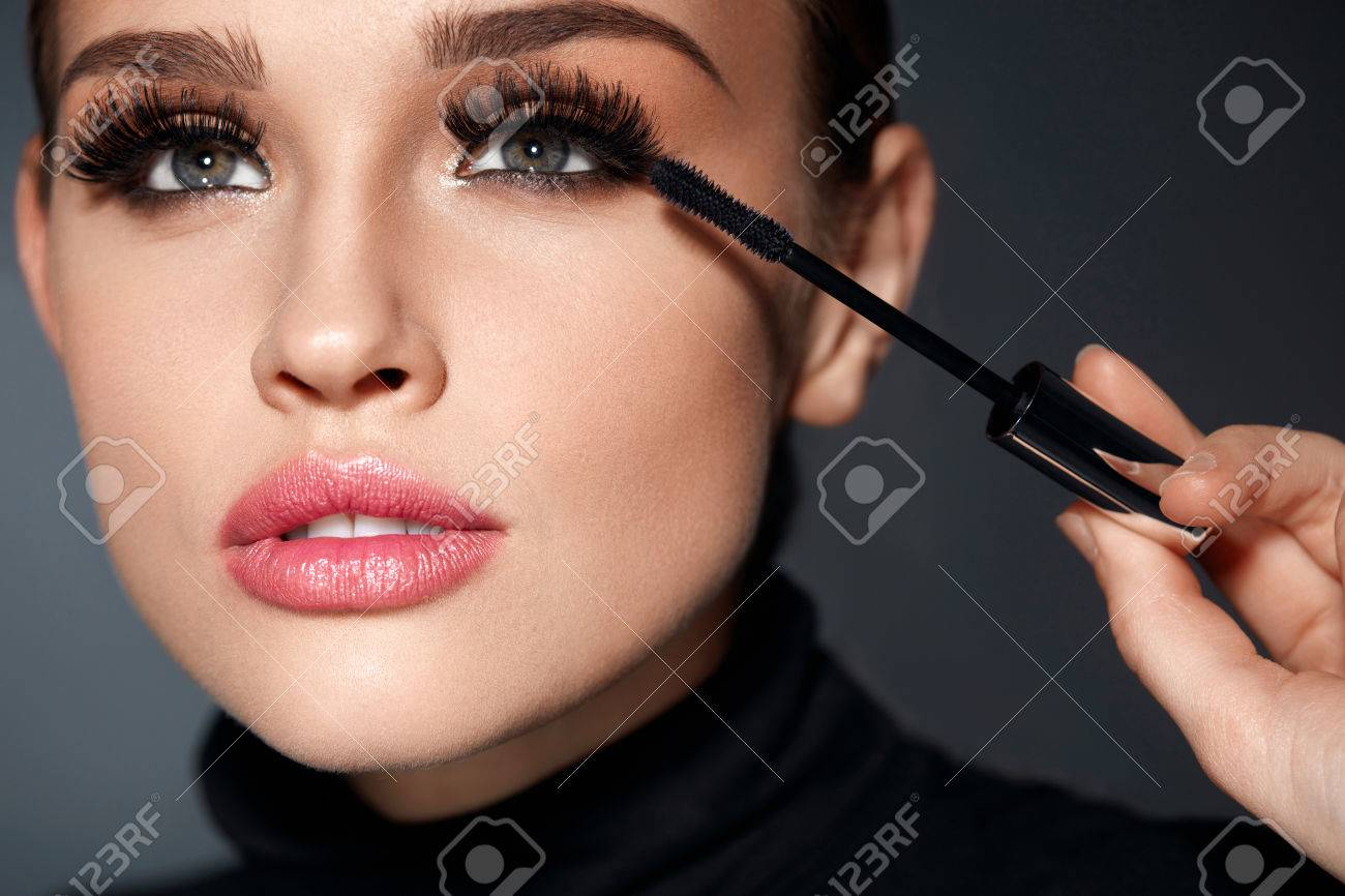 Beauty Make-up. Portrait Of Beautiful Young Woman With Fake Eyelashes Applying Black Mascara On Lashes, Holding Brush In Hand. Sexy Female With Soft Skin And Perfect Makeup. Cosmetics. High Resolution - 71353636