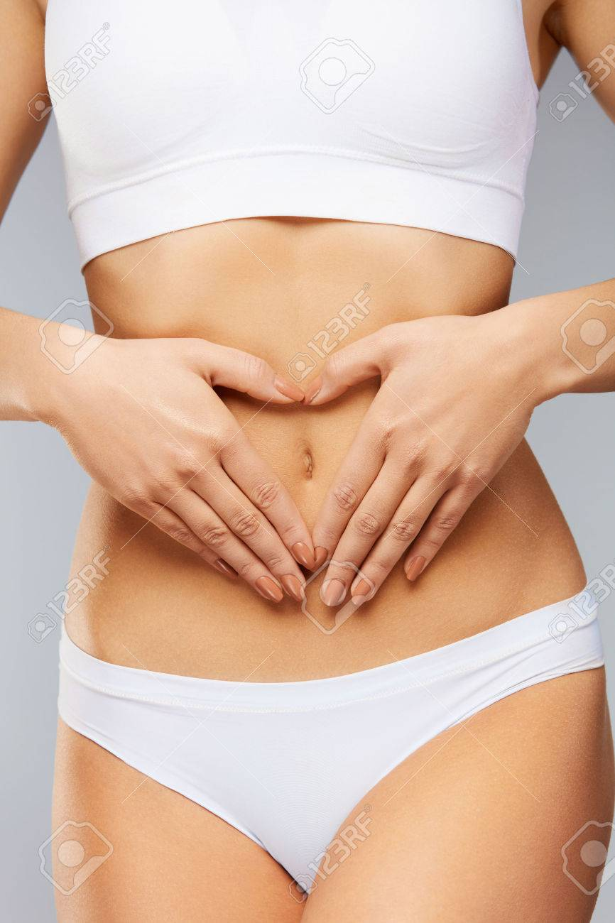 Female Health Care. ?loseup Healthy Young Woman With Beautiful Fit Slim Body, Perfect Smooth Soft Skin In White Panties Holding Hands On Stomach. Good Digestion, Women Health Concept. High Resolution Stock Photo - 74374454