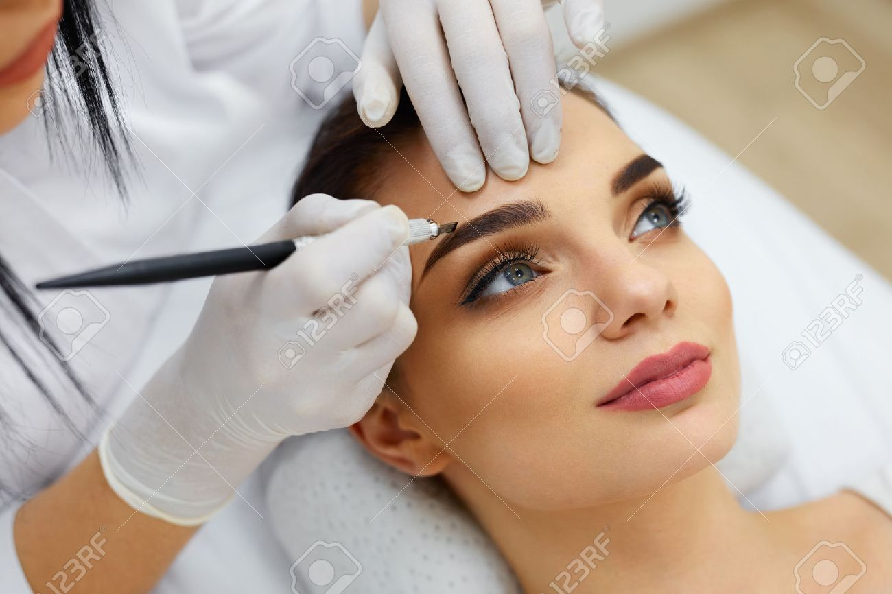 348c3fa84 Make-Up. Beautician Hands Doing Eyebrow Tattoo On Woman Face.Permanent Brow  Makeup