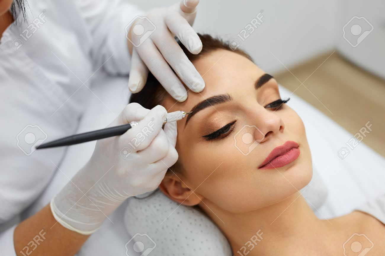 Permanent Makeup For Eyebrows. Closeup Of Beautiful Woman With Thick Brows In Beauty Salon. Beautician Doing Eyebrow Tattooing For Female Face. Beauty Procedure. High Resolution - 74803575