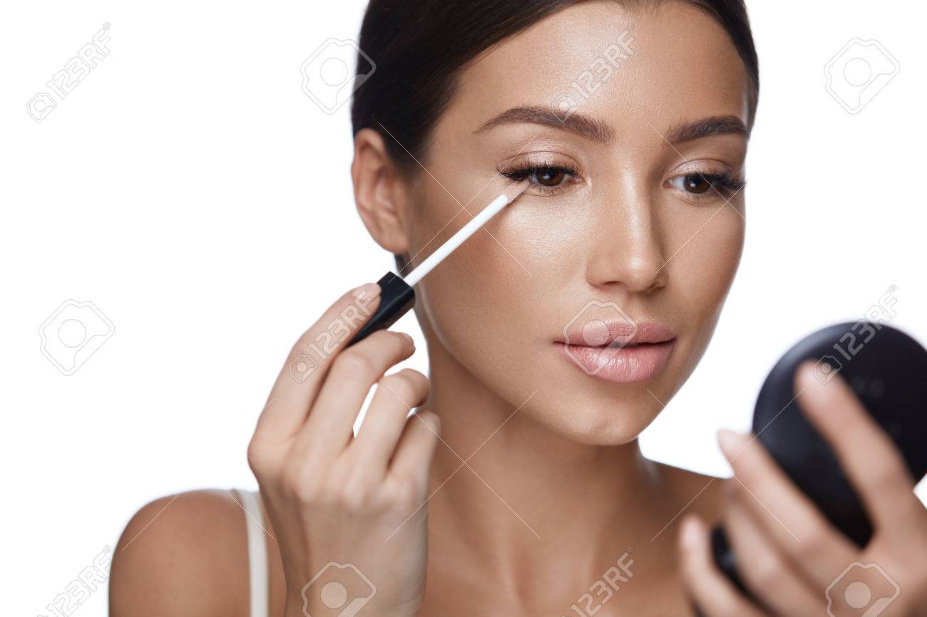 Beauty Face Closeup Of Sexy Young Woman With Concealer Brush And Mirror In Hands
