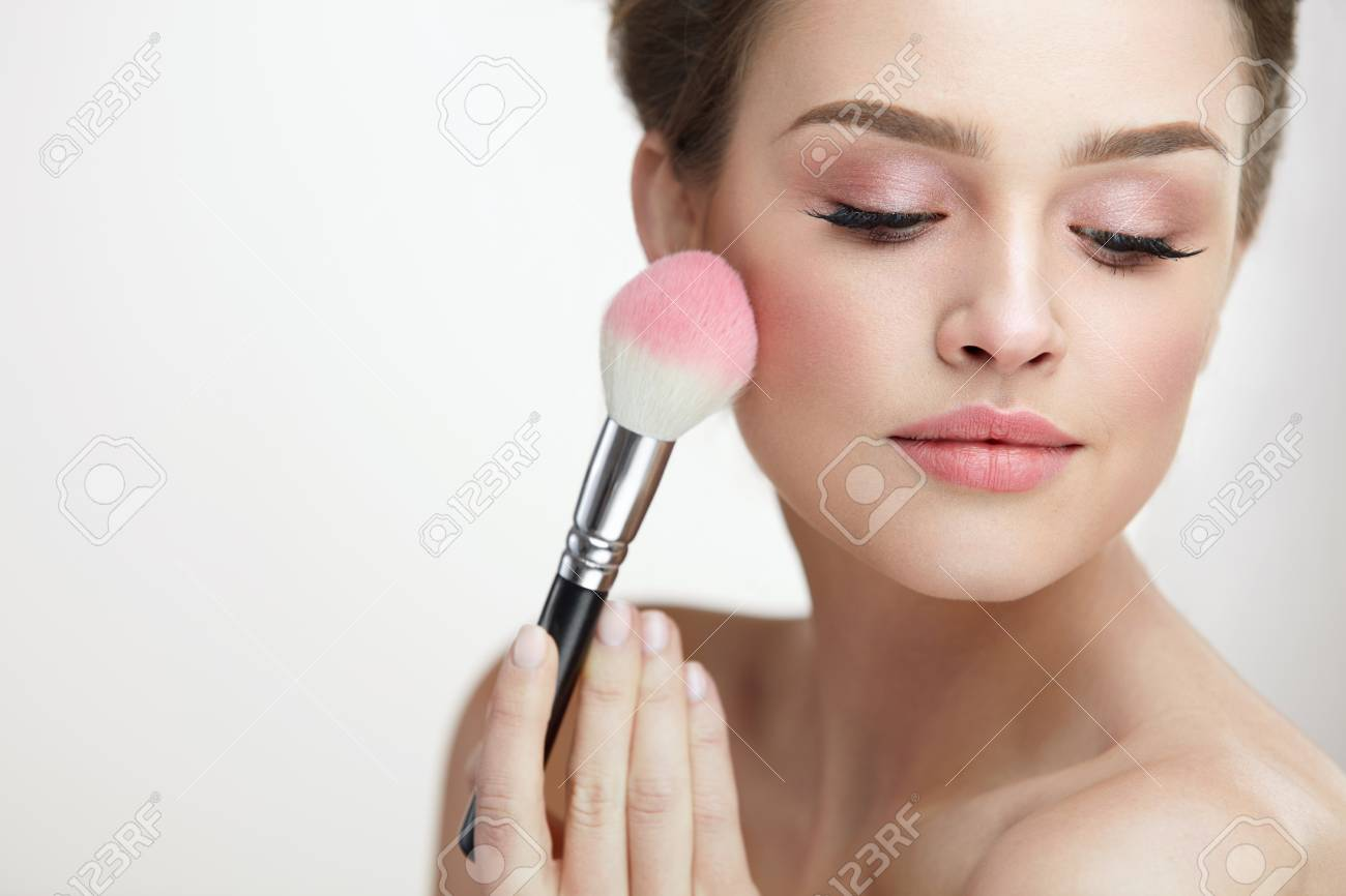 Facial Beauty Cosmetics. Portrait Of Attractive Female With Pure Soft Skin Applying Pink Loose Blush On Face. Closeup Of Beautiful Sexy Woman With Fresh Makeup Holding Cosmetic Brush. High Resolution - 79355341