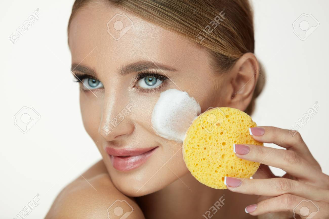 Beauty Face Care. Closeup Smiling Young Woman Using Washing Foam Cleanser And Sponge To Remove Makeup. Portrait Of Beautiful Girl Cleaning Fresh Skin With Face Wash Cosmetic Products. High Resolution - 90744695