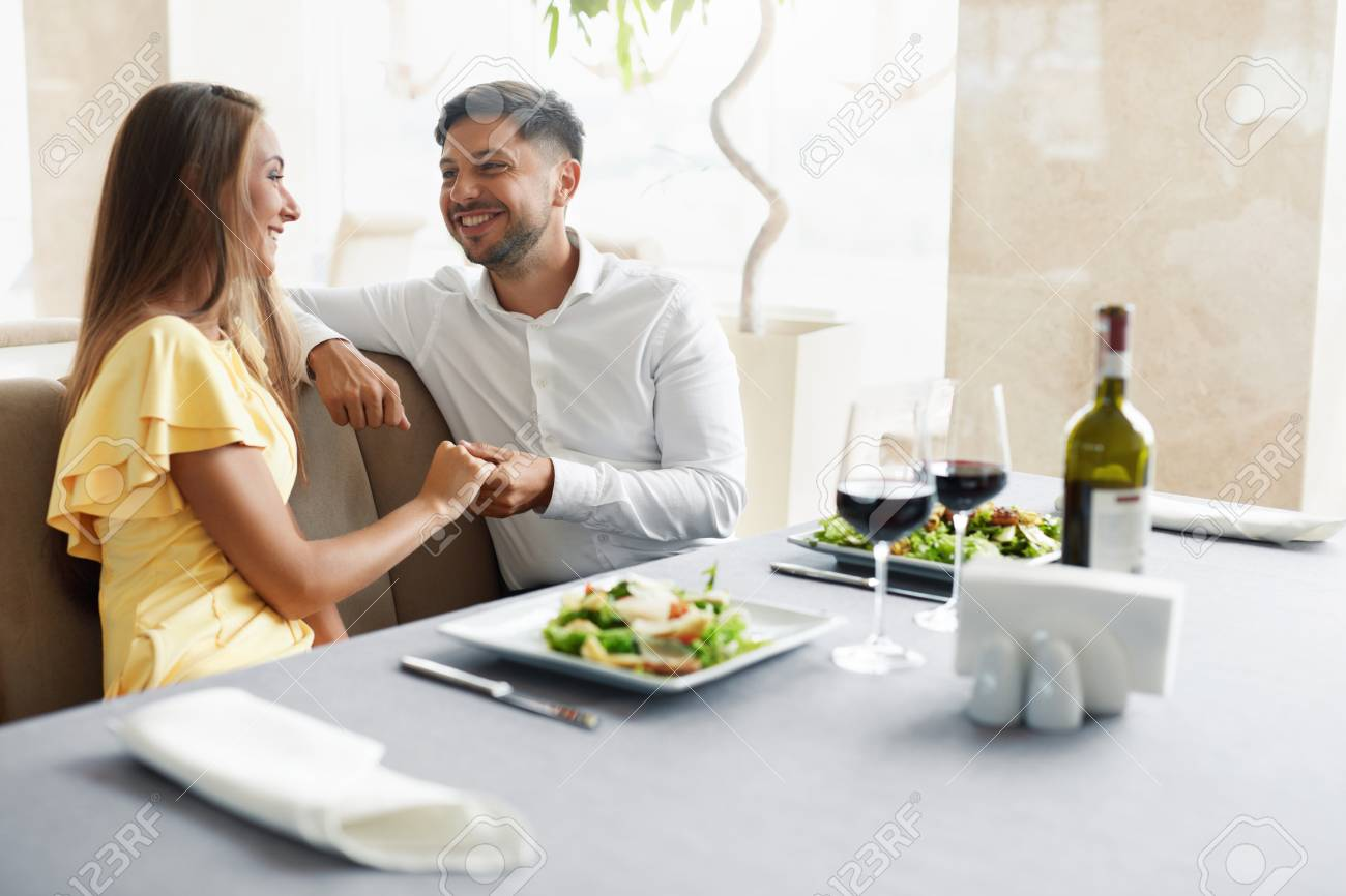 Romantic Couple Having Dinner For Two In Restaurant. Beautiful Happy People In Love Talking, Laughing, Flirting While Having Romantic Date With Wine And Food In Luxury Restaurant. High Quality Image. - 92440059