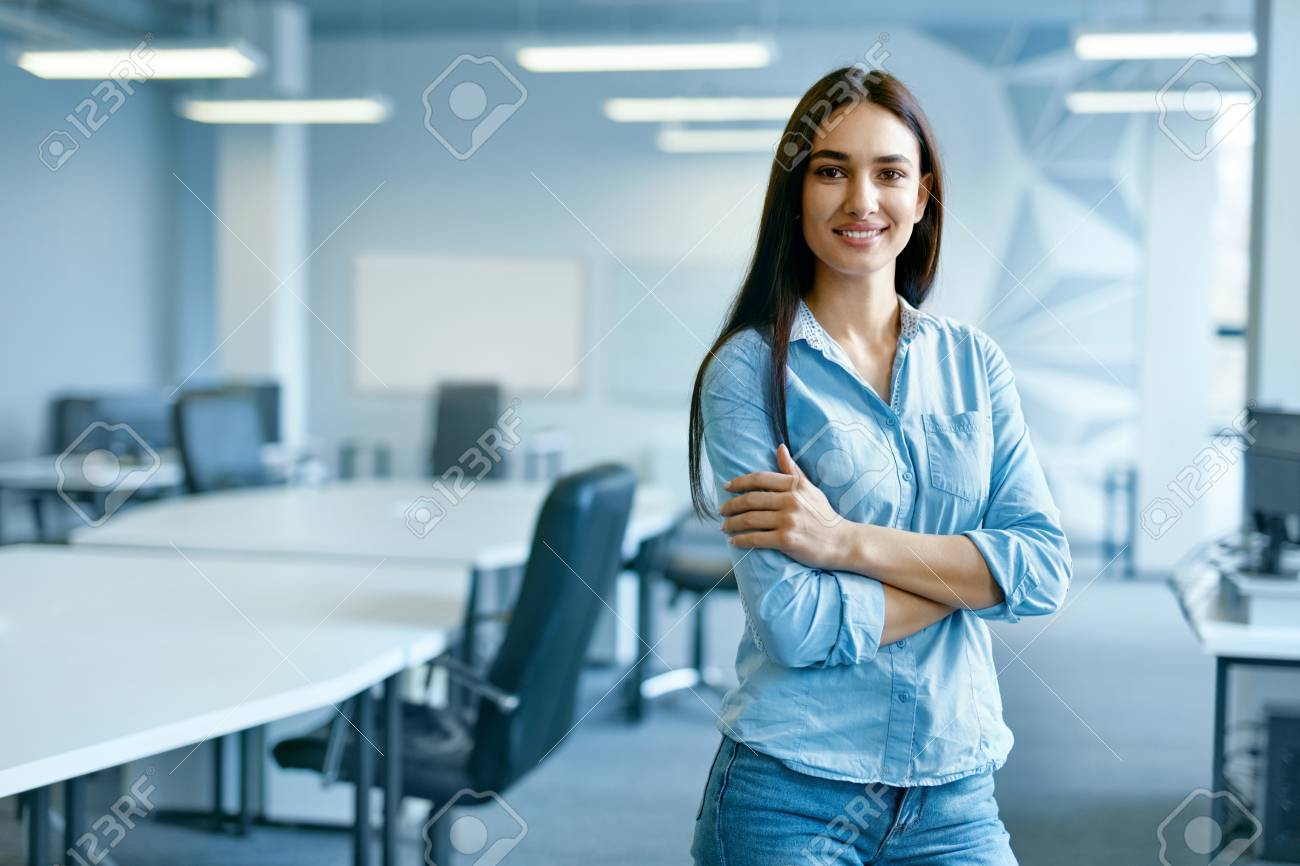 Woman In Office. Female At Work In Light Modern IT Office. Portrait Of Beautiful Smiling Young Worker In Casual Clothes With Arms Crossed At Workplace. Business Person, People At Work. High Quality - 96381531