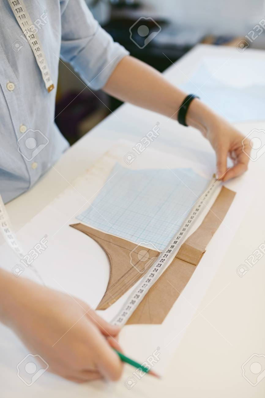 Female Tailor With Tape Measuring Sewing Pattern On Table In.. Stock ...
