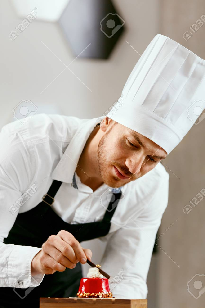 Male Pastry Cook In Apron And White Chef Hat Decorating Dessert Stock Photo Picture And Royalty Free Image Image 101262246