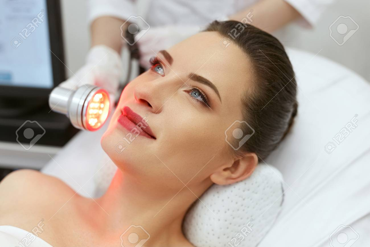 Cosmetology. Woman On Facial LED Red Light Therapy At Clinic. Cosmetologist Using Red Light For Skin Treatment. High Resolution - 108158067
