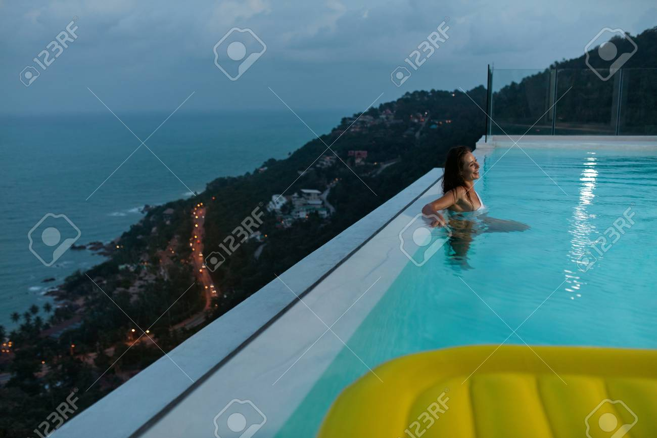 Woman relaxing in infinity swimming pool in evening on summer..