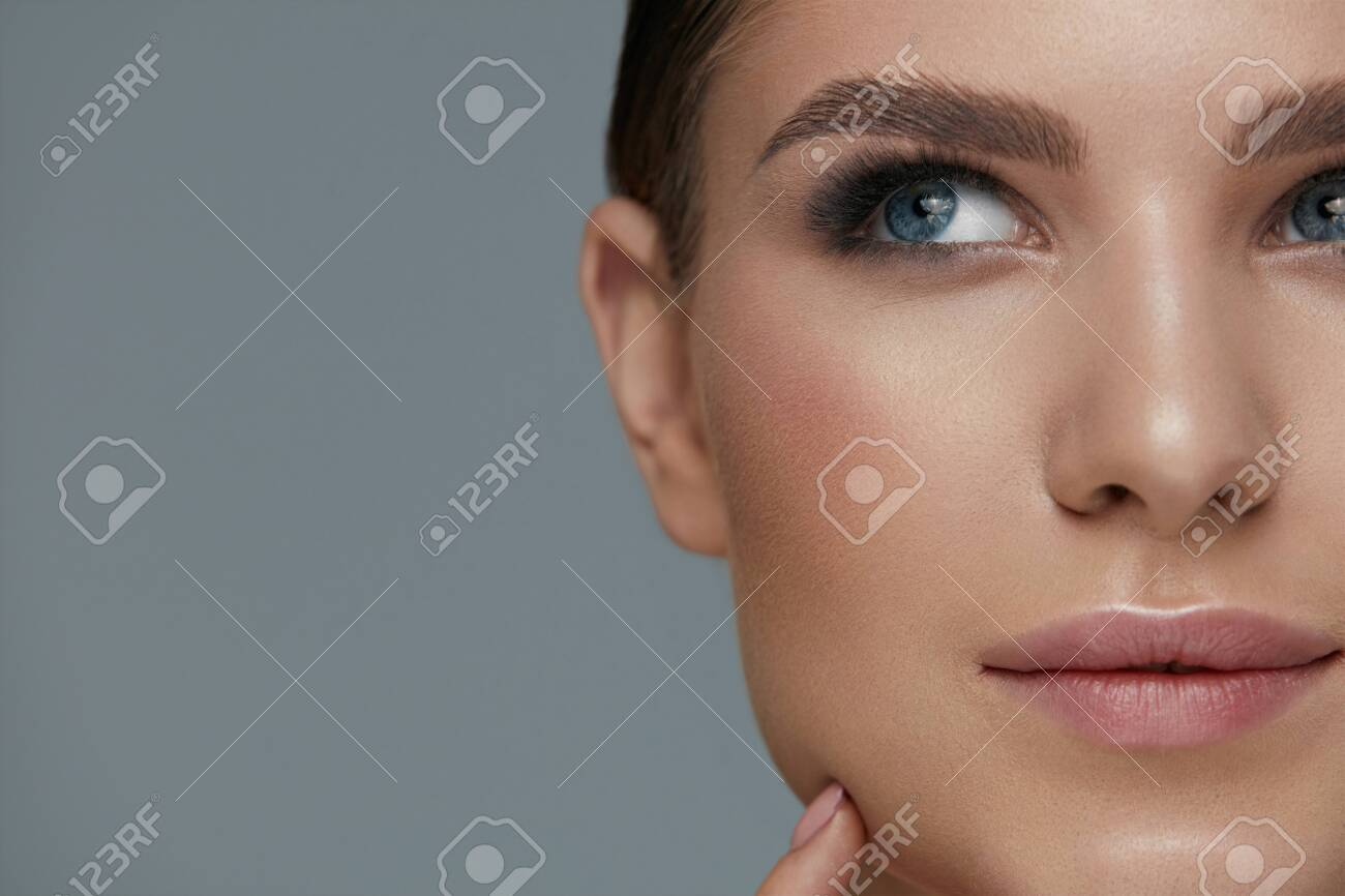 Beauty makeup. Woman face with beautiful eyes and eyebrows make-up and long black eyelashes closeup - 124516125