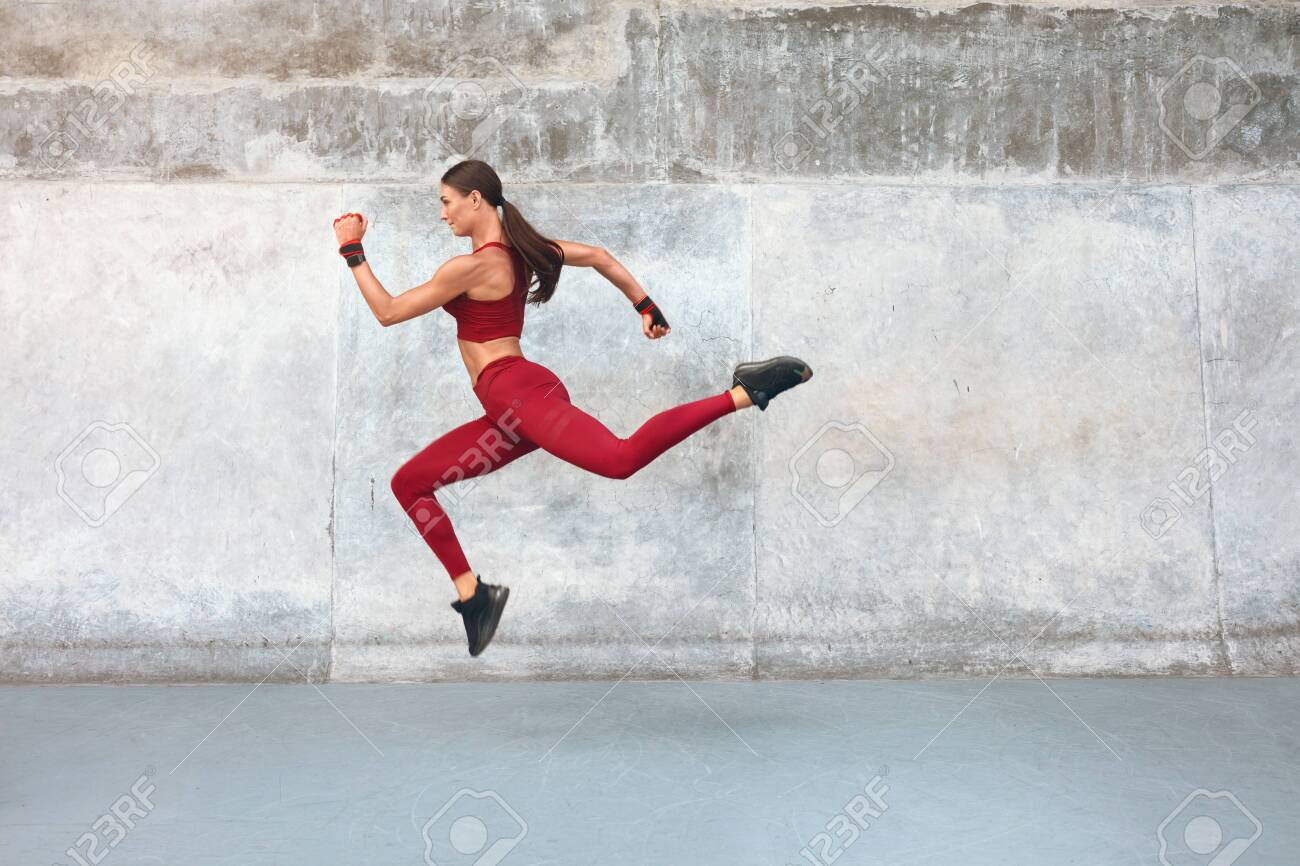 Fitness Girl Jumping. Outdoor Workout Against Concrete Wall At Stadium. Fashion Sporty Female With Strong Sexy Body In Dynamic Action Pose. Sport For Active Urban People. - 151409132