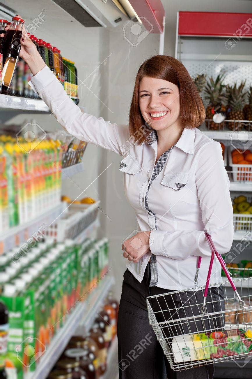 Woman in a supermarket choosing bottle of juice Stock Photo - 13698255