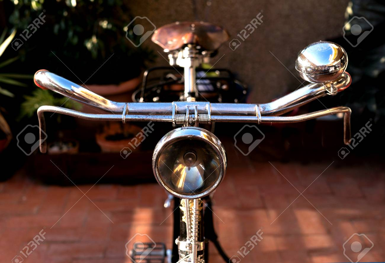 Vintage bike handlebar, with an antique light beacon, bell, brakes