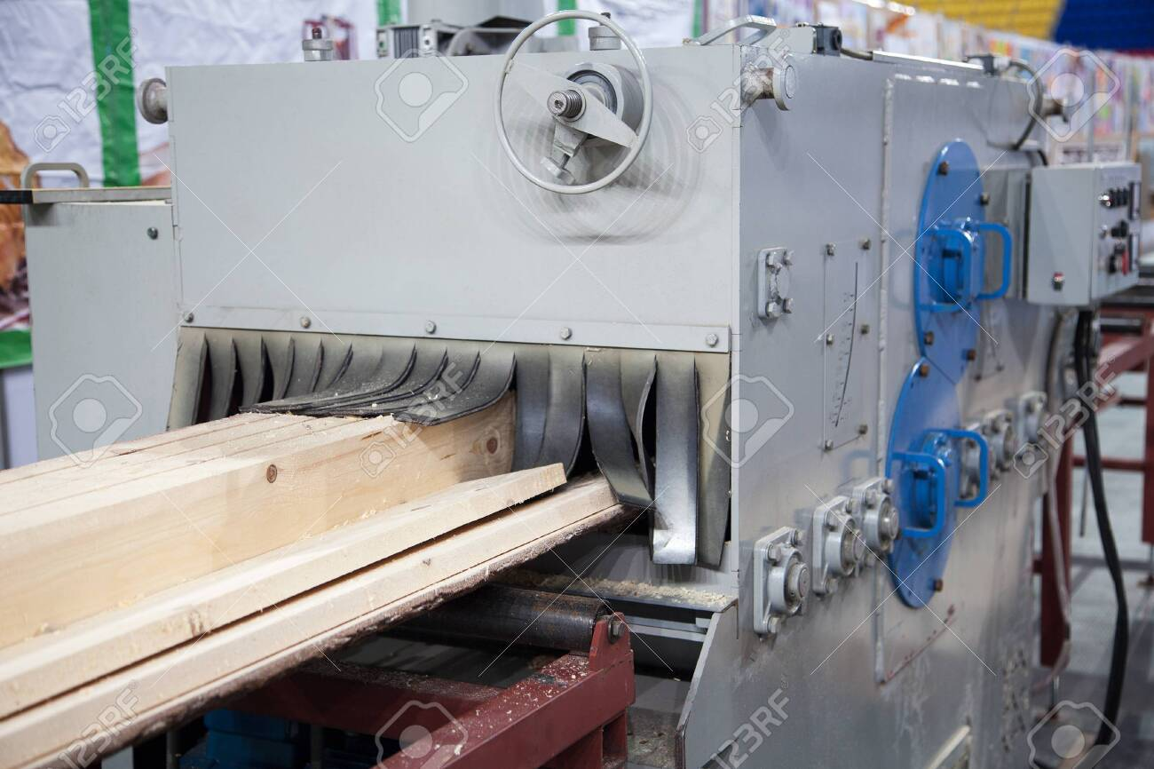 Big industrial sawmill cutting wood into boards. Woodworking facility producing lumber - 124574776