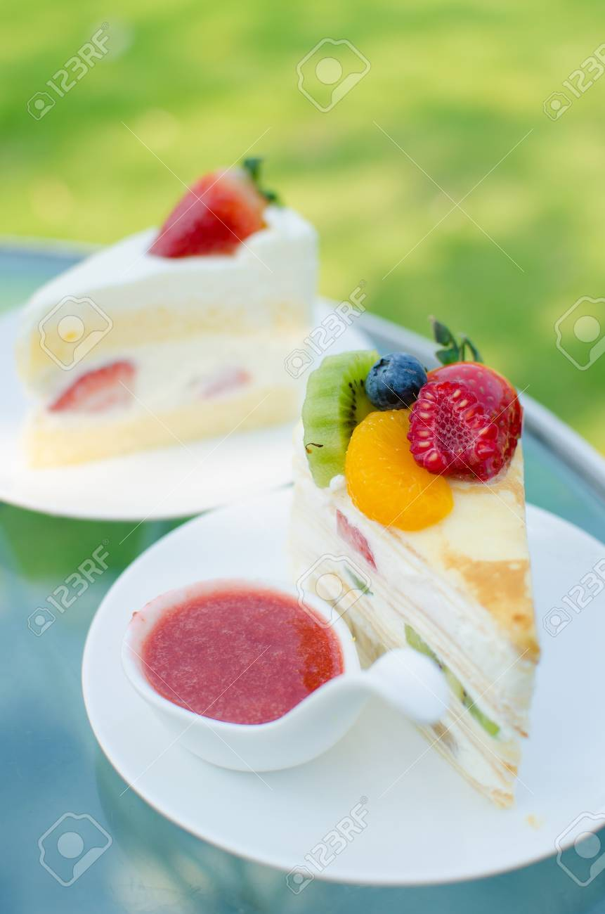 sweet cake with fruits on plate and green background Stock Photo - 18506662