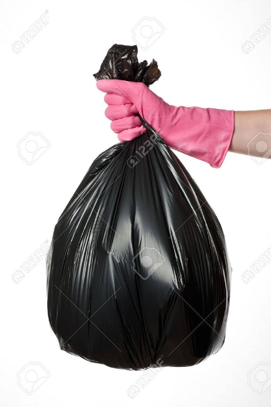 Hand holding a full black plastic trash bag - 18904251