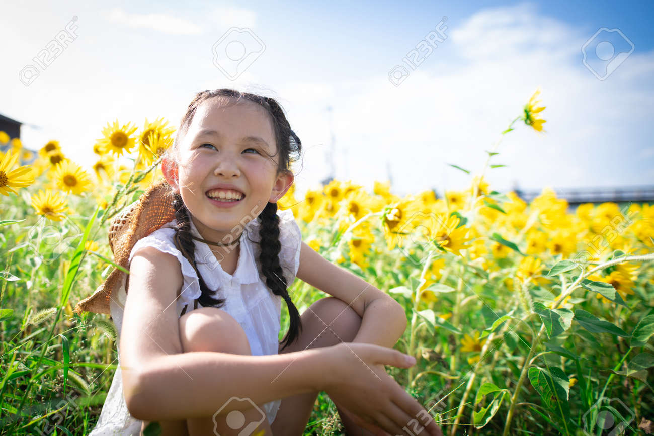 Girl playing in the sunflower field - 155183730