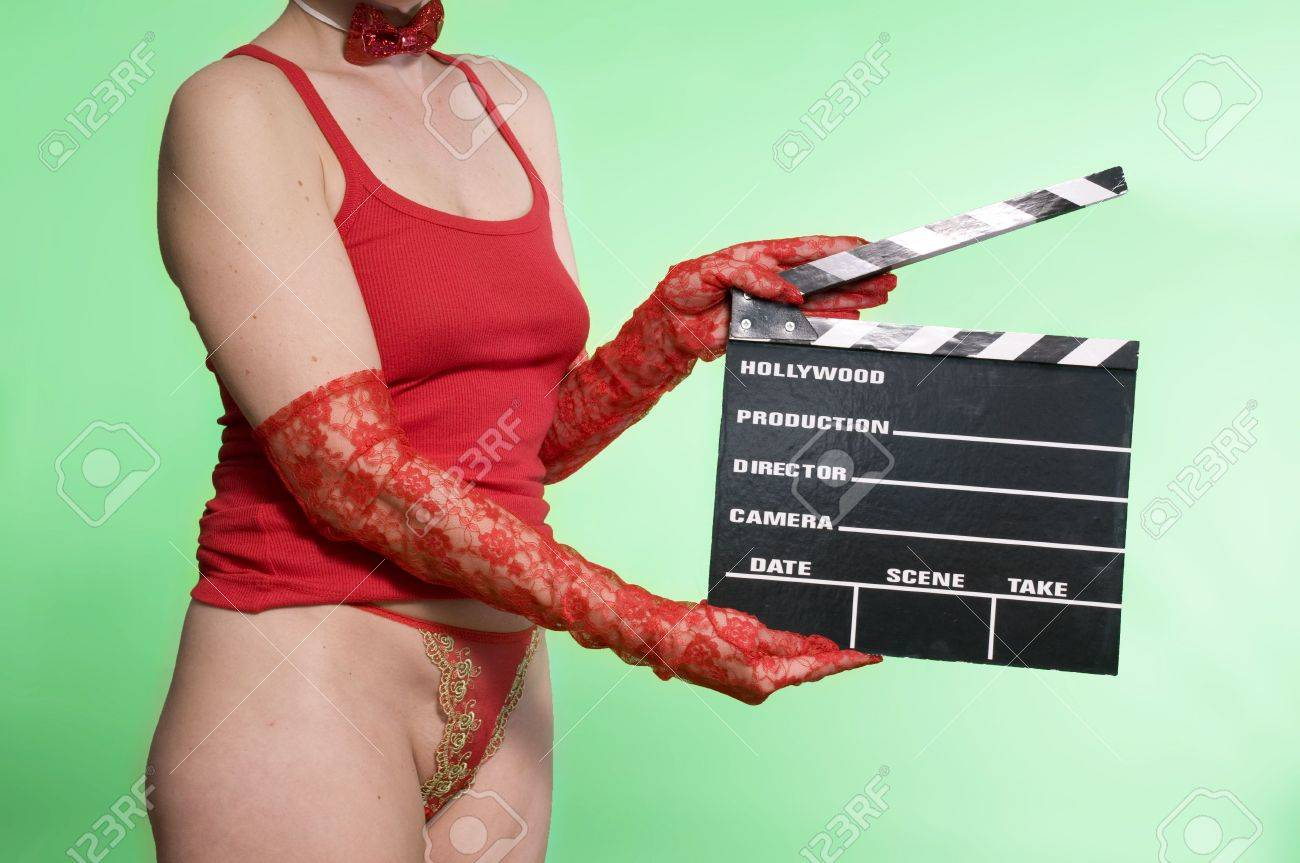 sexy young woman holding a movie clapper against a green screen Stock Photo - 4594318