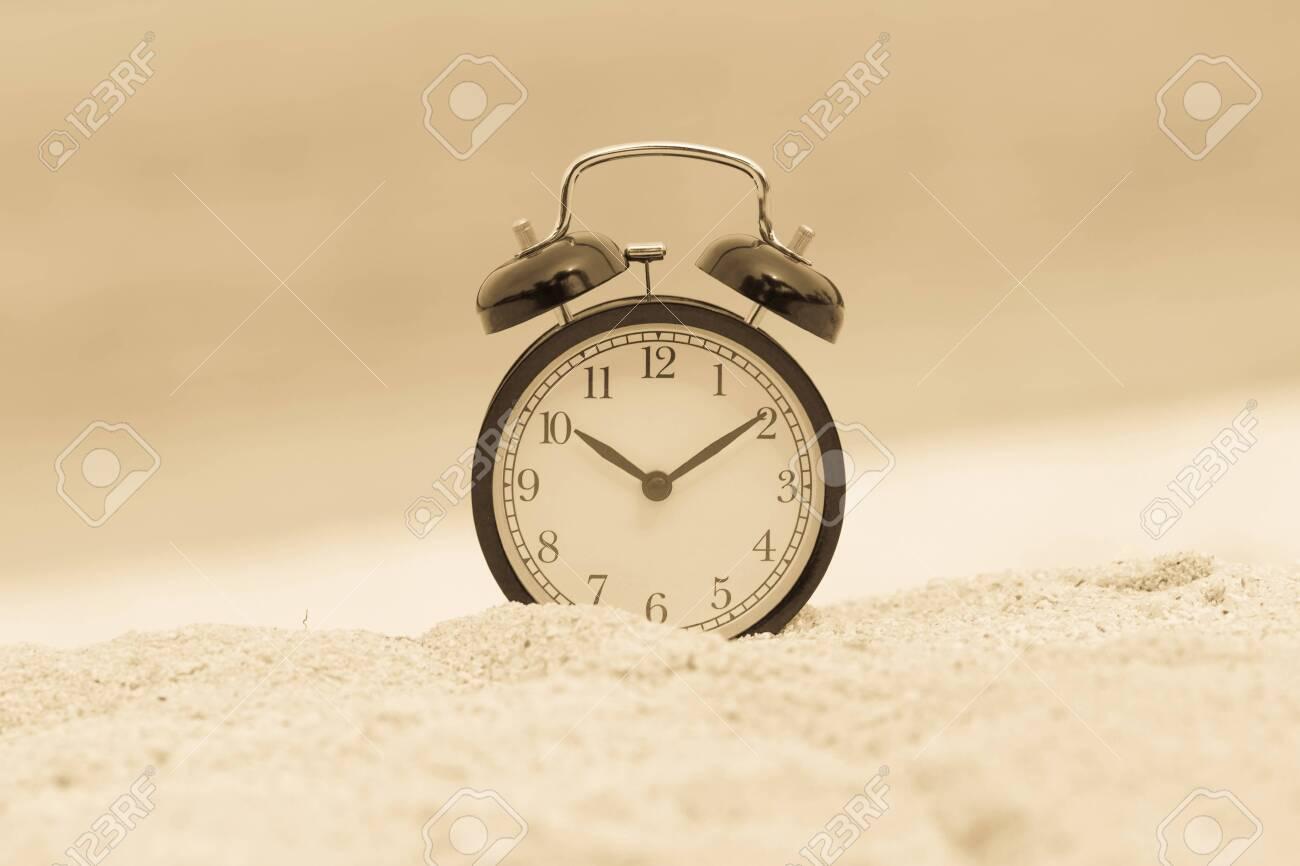 Vintage alarm clock on sand beach - 122679114